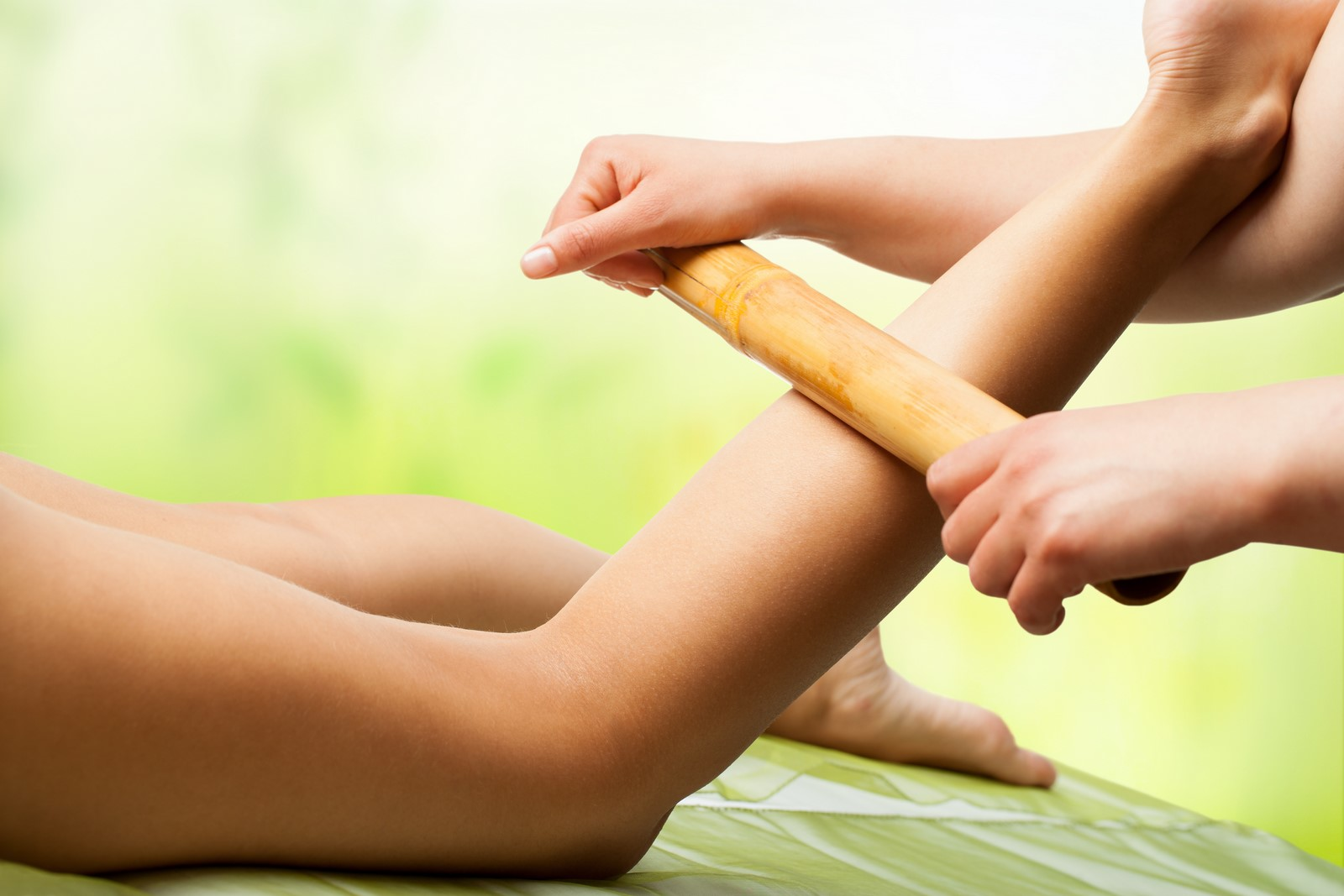 Close up of female hands doing bamboo massage on woman's legs.
